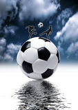 Football kick. Football - kick, focus on ball with water in back ground Royalty Free Stock Image