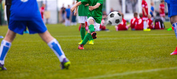 Football kick. Soccer ball in motion. Young soccer player Royalty Free Stock Images
