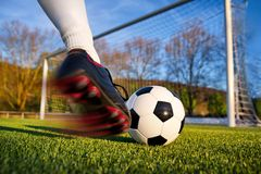 Football kick. Football or soccer shot with a neutral design ball being kicked, with motion blur on the foot and natural background Royalty Free Stock Photo