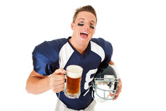 Football: Laughing Player with Beer. Caucasian American football player, in uniform, isolated on white, with various related props Royalty Free Stock Images