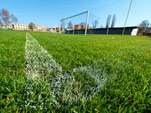 Football line on playfield grass. Soccer ball green grass field, soccer line. Hang bended blue yellow soccer nets, soccer football net Stock Photo