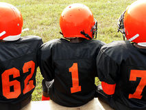 Football - little league players. Photo of little league football players sitting on a sidelines bench awaiting their turn to play stock image