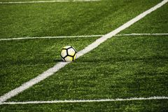 Football lying on a green field with artificial turf on a beauti Royalty Free Stock Images