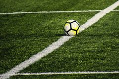Football lying on a green field with artificial turf on a beauti Royalty Free Stock Photography