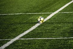 Football lying on a green field with artificial turf on a beauti Royalty Free Stock Photo