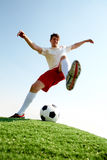 Football match. Portrait of soccer player before kicking ball on football field Royalty Free Stock Image