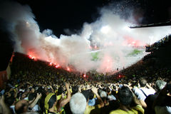 Football match between Aris and Boca Juniors. THESSALONIKI, GREECE - AUGUST 5: Fans and supporters of PAOK team light flares in football match between Aris and Royalty Free Stock Photography