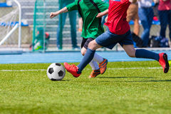 Football match for children. Training and football soccer tourna. Players playing football soccer game. Running players in grenn and red outfit sports uniforms Royalty Free Stock Photography
