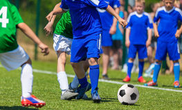 Football match for children. Young boys playing soccer game. Competition between two youth soccer teams. Boys in blue and green sport uniforms running and Royalty Free Stock Image