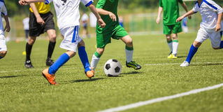Football match. Young boys play football soccer match. Running player of two teams. White and green uniforms Royalty Free Stock Photos
