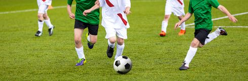 Football match for young players. Training and football soccer tournament for children. Youth soccer competition betweeen two footballers. White team versus Royalty Free Stock Photography