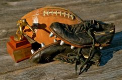 Football Memories. An old pair of shoes with spikes, leather football, and a trophy bring back memories of former days on the gridiron Stock Image