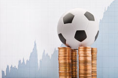 Football and money. Soccer ball on a financial report background Royalty Free Stock Image