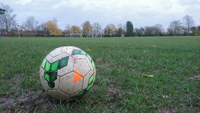 A football on a muddy football pitch Stock Image