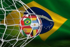 Football in multi national colours at back of net Royalty Free Stock Photos