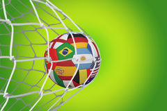 Football in multi national colours at back of net Royalty Free Stock Photo