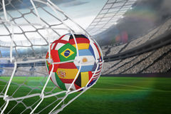 Football in multi national colours at back of net Royalty Free Stock Image