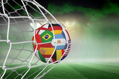 Football in multi national colours at back of net Stock Image