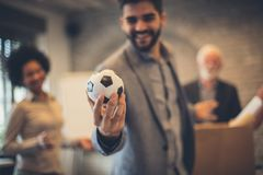 Football is my hobby. Businesspeople in the office. Man holding football ball. Focus on man royalty free stock image
