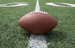 Football near the Fifty. Football centered and near the fifty yardline Royalty Free Stock Photos
