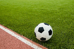 The football is near line on the artificial grass soccer field. Royalty Free Stock Photos