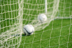 Football net with out-focus balls in background Stock Photo