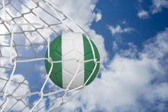 Football in nigeria colours at back of net Royalty Free Stock Photography