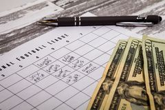 Football office pool grid for sports betting concept with cash. Football American office pool grid for sports betting concept with boxes, dollars, pen royalty free stock images