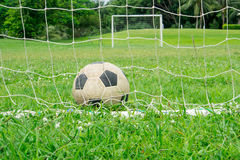 Football. Old leather football on green field royalty free stock photo