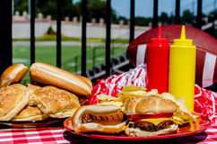 Football Party. With cheeseburger, hot dog, potato chips, pom poms, buns, and football.  Football field in background Royalty Free Stock Photo