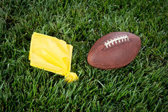 Football penalty flag. A yellow penalty flag and football lie motionless on a playing field Stock Photography