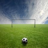 Football pitch with ball. A green grass football pitch with a black and white ball in front of the goal Stock Photo