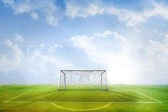 Football pitch and goal under blue sky Stock Photo