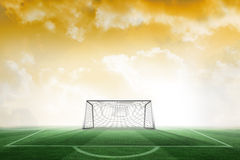 Football pitch and goal under yellow sky Stock Images