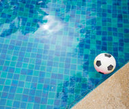 Football. A plastic football floating in the blue water of a swimming pool Royalty Free Stock Photo