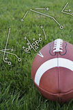 Football playbook. A close-up view of an american football on a grassy field with a playbook drawing (vertical Royalty Free Stock Images