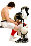 Football Player. American football player. Seated on weight bench, partially undressed after game royalty free stock image