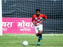 Football/Soccer player in action on green ground. A football player in action about to kick a ball. Goal Post in Background. Prakash Sonkar Smriti Gold Cup All stock photography