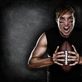 Football player aggressive with american football. Football player aggressive portrait holding american football on black blackboard background with copy space royalty free stock image