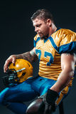 Football player with ball and helmet in hands Royalty Free Stock Image