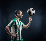 Football-player with a ball. Football-player spinning soccer ball over black background Royalty Free Stock Photography