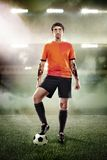 Football player with ball at the stadium. Football player in orange shirt with ball at the stadium royalty free stock image