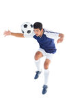Football player in blue heading ball Royalty Free Stock Image