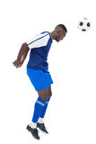 Football player in blue heading ball Royalty Free Stock Photography