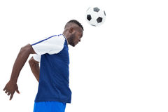 Football player in blue heading ball Stock Photography