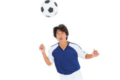 Football player in blue heading the ball Royalty Free Stock Image