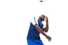 Football player in blue heading ball Stock Photo