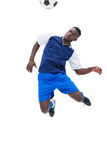 Football player in blue heading ball Stock Image