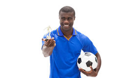 Football player in blue holding ball and figurine Royalty Free Stock Image