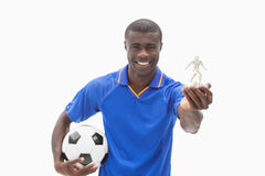 Football player in blue holding ball and figurine Stock Images